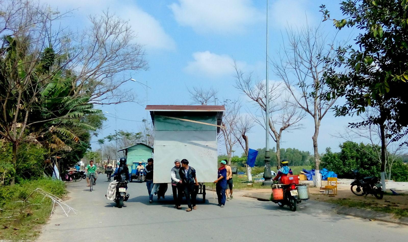 Các hộ dân di dời lều, trại, vật dụng che chắn để hoàn trả lại mặt bằng vỉa hè đường Bạch Đằng. Ảnh: XUÂN KHÁNH