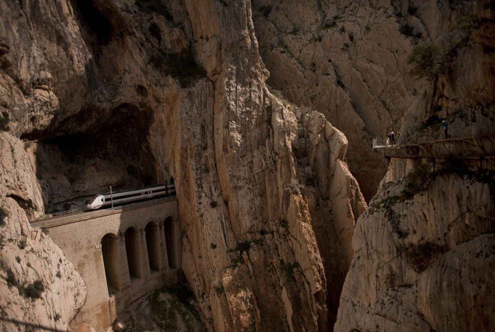 "A train passes through a tunnel in the rocks as people walk the foot-path ""El Caminito del Rey,"" or King's little path, a narrow walkway hanging and carved on the steep walls of a defile in Ardales near Malaga, Spain, on March 15, 2015. #  Jorge Guerrero / AFP / Getty"