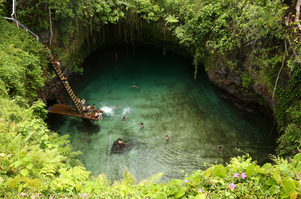 Vistors swim in the To Sua Ocean Trench on September 12, 2015, in Lotofaga, Samoa. The To Sua Ocean Trench with a literal translation in English of