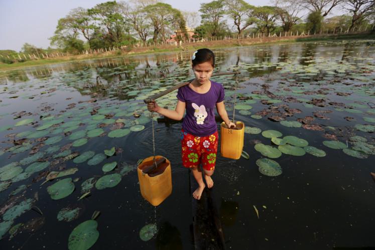 A girl collects drinking water at Dala River outside Yangon, Burma, on March 3, 2016. #  Soe Zeya Tun / Reuters