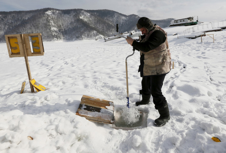 An employee at a boat station drills a hole in the frozen surface of the Yenisei River to draw fresh water for cooking and drinking, outside Krasnoyarsk, Siberia, Russia, on March 2, 2016. #  Ilya Naymushin / Reuters
