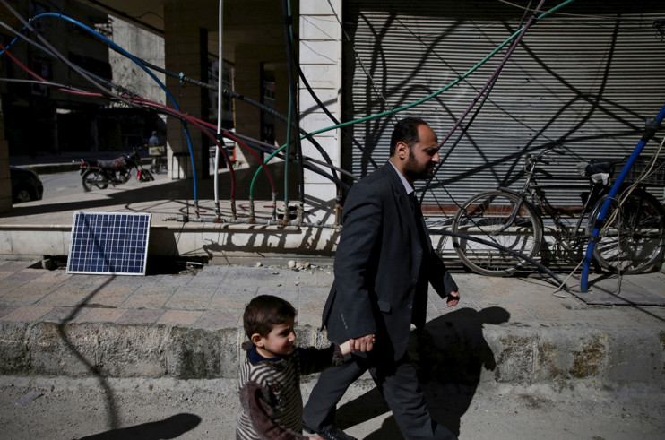 Residents walk past water pipes in the rebel-held Douma neighbourhood of Damascus, Syria, on March 7, 2016. #  Bassam Khabieh / Reuters