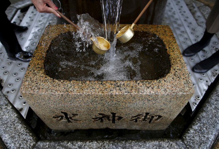 """Visitors scoop water using traditional ladles at a natural spring water spot known as the """"divine water"""" at Daikyoji Temple, also called Shibamata Taishakuten, in Tokyo, Japan, on March 6, 2016. Local residents drink the water or rinse their mouths, and wash their hands to purify themselves, and wish for good fortune. #  Issei Kato / Reuters"""