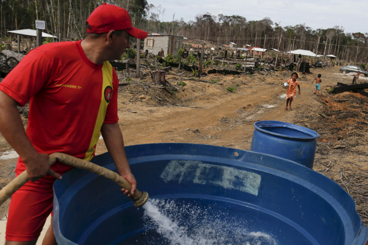 A civil defense worker pours water from a water truck into a container near a dry lake in Presidente Figueiredo, in the Amazonas state, Brazil, on March 4, 2016. #  Bruno Kelly / Reuters