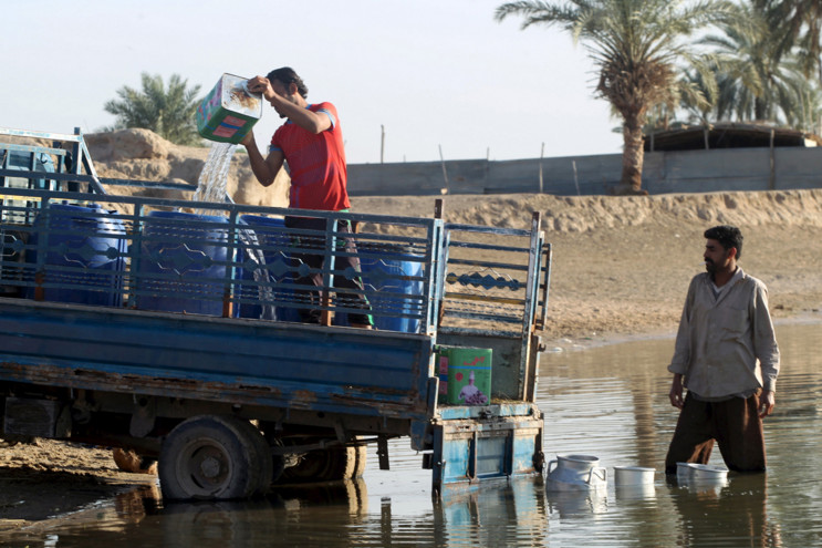 Men collect water from the Euphrates river in Najaf, south of Baghdad, Iraq, on March 7, 2016. #  Alaa Al-Marjani / Reuters