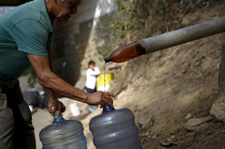 A man places his bottles to be filled with water dripping from a spring next to a highway along the Avila mountain in Caracas, Venezuela, on March 3, 2016. #  Carlos Garcia Rawlins / Reuters