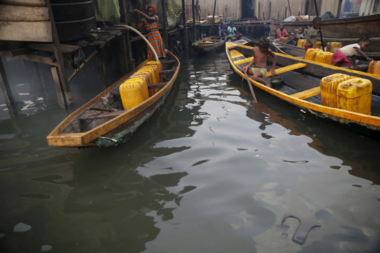 People fetch water in containers in canoes at a water selling point in the Makoko fishing community on the Lagos Lagoon, Nigeria, on February 29, 2016. #  Akintunde Akinleye / Reuters