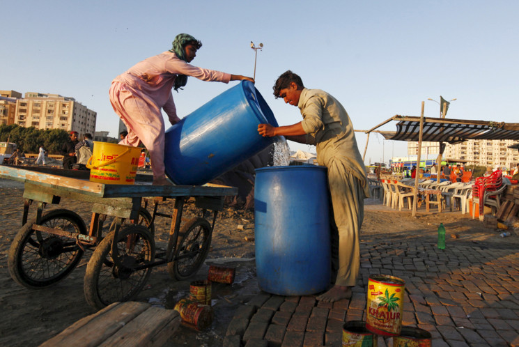 Men pour water brought by cart into a container at a stall on Clifton Beach in Karachi, Pakistan, on March 5, 2016. #  Akhtar Soomro / Reuters