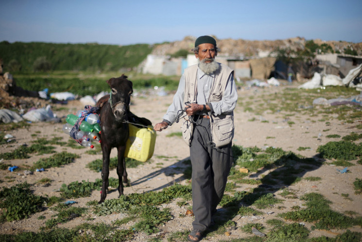 A Palestinian man pulls his donkey loaded with empty bottles and a jerrycan, as he makes his way to fill them with drinking water, in Khan Younis, in the southern Gaza Strip, on March 1, 2016. #  Ibraheem Abu Mustafa / Reuter / REUTERS