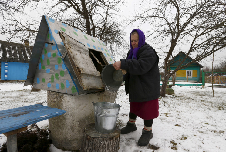 A woman fills a bucket with drinking water from a well in the village of Rum, Belarus, on March 4, 2016. #  Vasily Fedosenko / Reuters