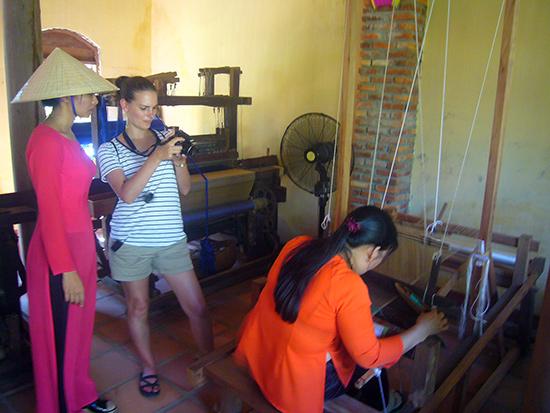Du khách tham quan, tìm hiểu nghề dệt của người Việt tại Làng lụa Hội An. Ảnh: Đ.HUẤN
