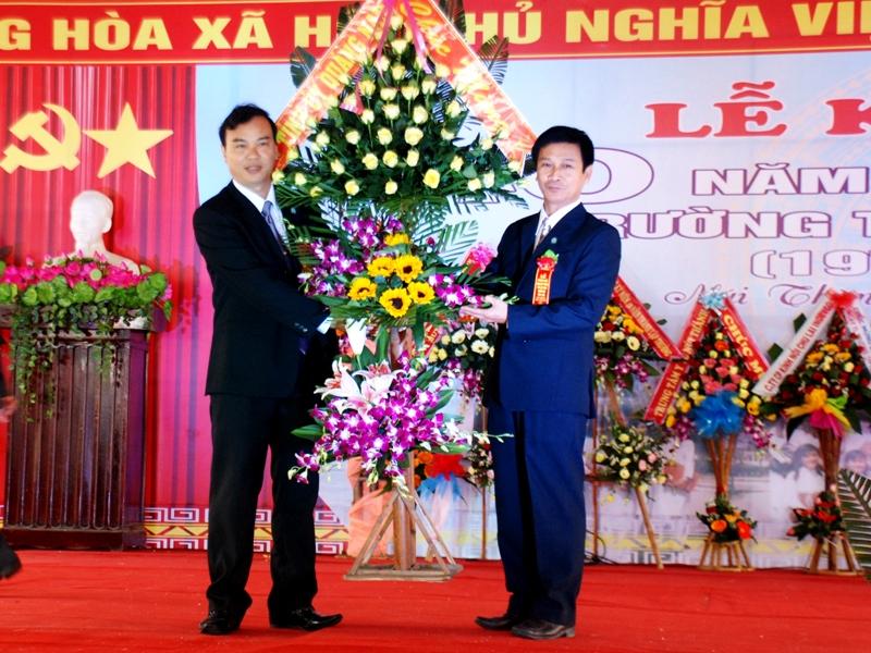 Đồng chí Đoàn Ngọc Thi - Phó Trưởng ban Tuyên giáo Tỉnh ủy tặng hoa chúc mừng nhà trường. Ảnh: Đ.ĐẠO