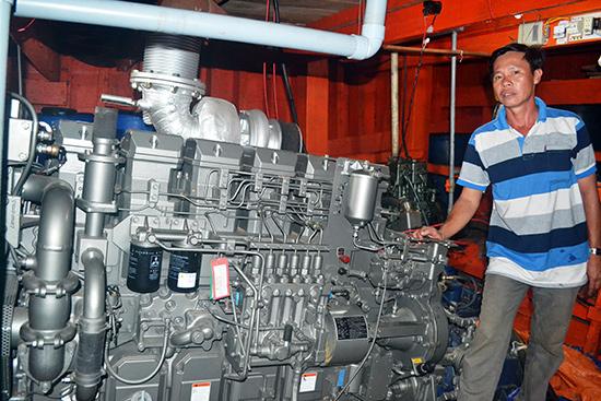 Ông Lương Tấn Xị bên máy thủy mới của tàu cá QNa-91739. Mua máy thủy đó sử dụng, ông Xị phải đóng thuế 250 triệu đồng mà không được hoàn lại.