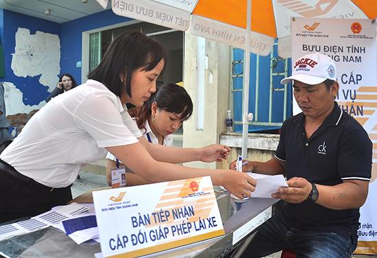 Người dân làm thủ tục cấp đổi GPLX tại Bưu cục Điện Ngọc.