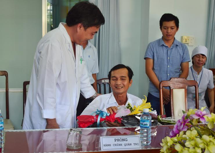 Bác sĩ Phạm Ngọc Ẩn - Giám đốc Bệnh viện Đa khoa Quảng Nam tặng hoa chúc mừng bệnh nhân Nguyễn Văn Dũng.
