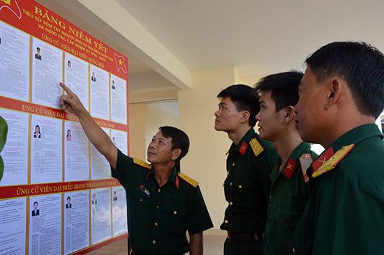 Cán bộ, chiến sĩ 4 cơ quan Bộ Chỉ huy tìm hiểu tiểu sử những người ứng cử đại biểu Quốc hội khóa XIV và đại biểu HĐND các cấp. Ảnh: TUẤN ANH