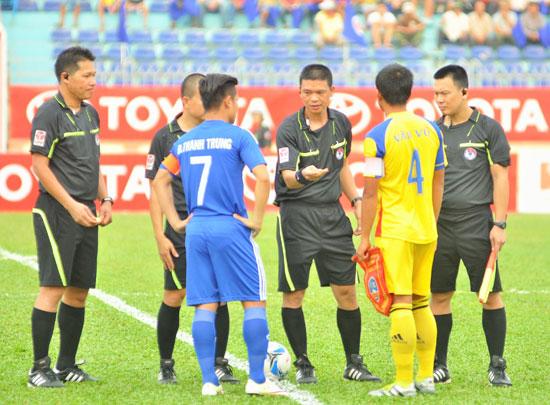 Trọng tài Hà Anh Chiến (đứng giữa đang làm thủ tục chọn sân) trong trận QNK Quảng Nam gặp Sana Khánh Hòa.Ảnh: T.V