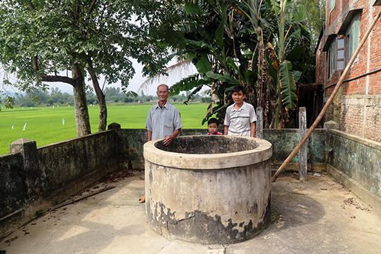 Ông Trần Cường (trái) và ông Hai Cổn kể chuyện xưa bên giếng Cửu Tý. Ảnh: V.T.L