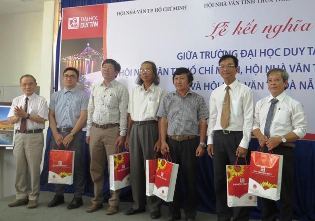 Nhà trường trao quà lưu niệm cho đại diện các hội nhà văn, nhà xuất bản. Ảnh: Hoàng Liên
