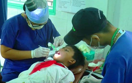 Các tình nguyện viên của đoàn cùng thăm khám, chăm sóc răng miệng cho các em miền núi. Ảnh: NGUYÊN - KHANH