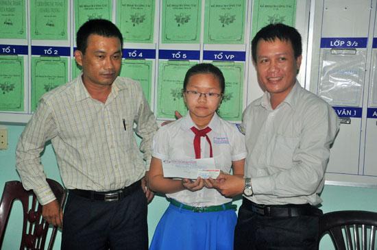 Ông Nguyễn Văn Nghiệp - Giám đốc Trung tâm Anh ngữ Galaxy (bên phải) và ông Vũ Từ Long - Giám đốc Công ty TNHH phát triển công nghệ tin học Vũ Long tặng quà cho em Nguyễn Thu Hà.