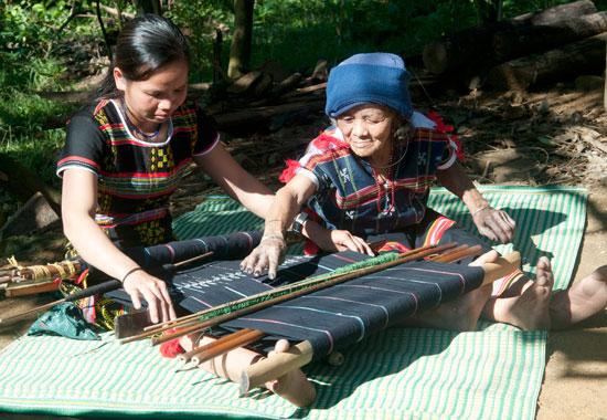 Cụ bà Tơngôl Adớp  đang truyền dạy kỹ thuật dệt hoa văn gợn sóng cho thợ dệt trẻ của làng Công Dồn. Ảnh: T.V