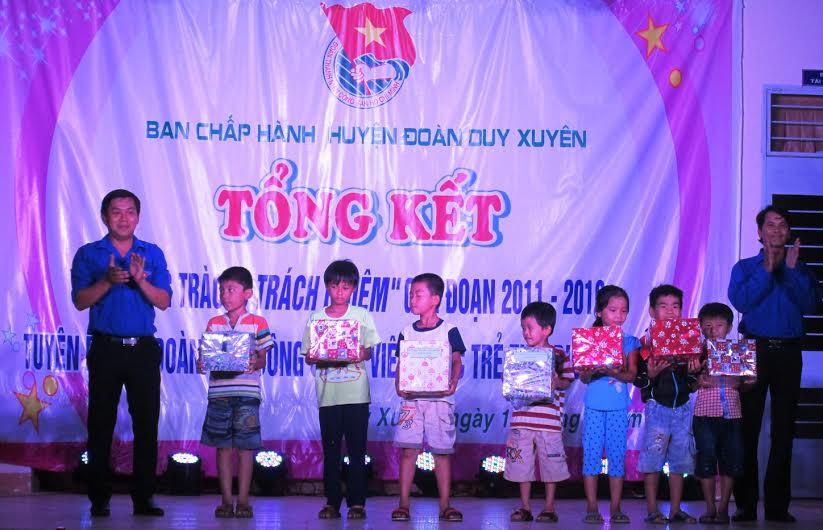 Tặng quà cho các em học sinh nghèo vượt khó học giỏi tại buổi lễ. Ảnh: HOÀI NHI