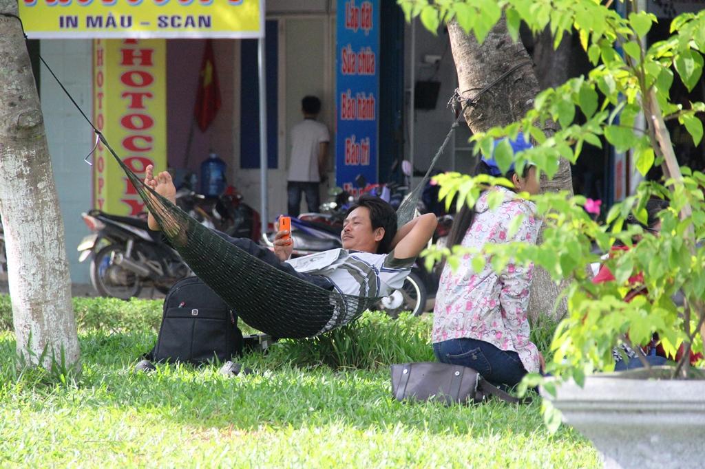 Một phụ huynh cột võng nằm nghỉ dưới gốc cây bên vệ đường gần khu vực thi. Ảnh: ALĂNG NGƯỚC