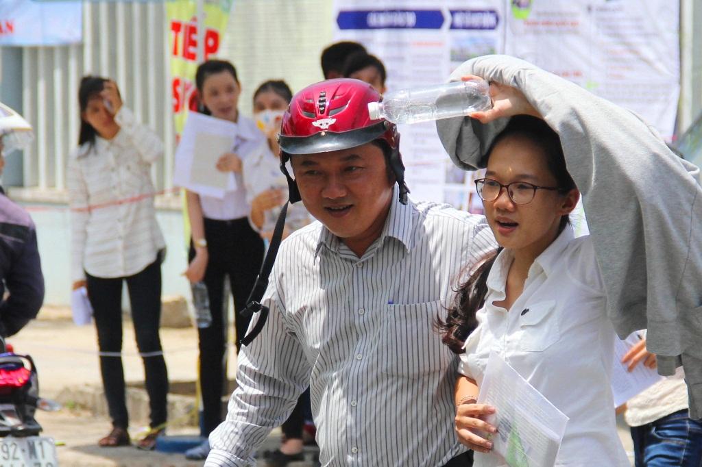 Một ông bố vội vã đón con từ cổng của điểm thi Trường Đại học Quảng Nam, rồi dắt qua đường an toàn. Ảnh: ALĂNG NGƯỚC