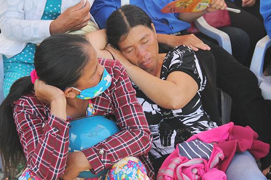Bà Nguyễn Thị Lý dựa vào vai một phụ huynh, vội chợp mắt trước điểm thi để đợi con về. Ảnh: ALĂNG NGƯỚC