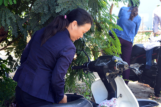 Thí sinh tuổi 41 - Phan Thị Thanh Tâm lụi hụi dắt xe để sang điểm thi khác đón con gái cũng thi tốt nghiệp THPT năm nay. Ảnh: Q.Tuấn