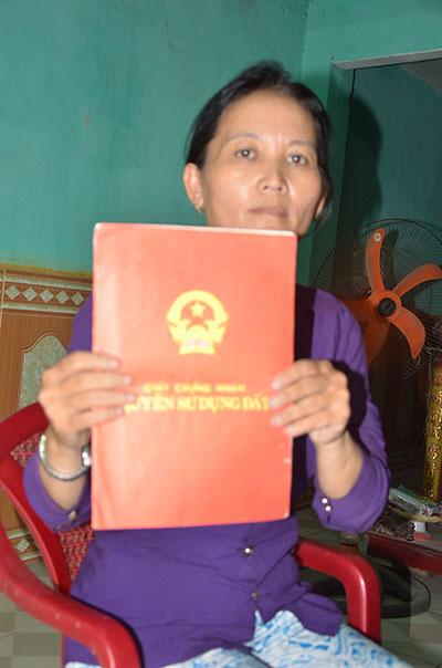 Bà Tám với bìa đỏ ghi diện tích của 2 thửa đất được Nhà nước công nhận quyền sở hữu sử dụng năm 1998. Ảnh: T.H