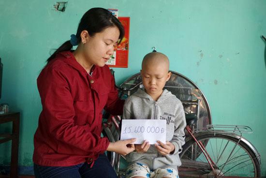 Bạn đọc báo Quảng Nam trao tiền ủng hộ cháu Đinh Thị Kim Ngọc. Ảnh: NHƯ TRANG