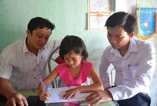 Cán bộ đoàn huyện Thăng Bình giúp em Nguyễn Thị Hoàng Tú rèn chữ. Ảnh: N.Q.V