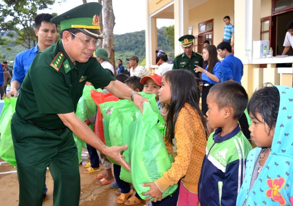 Đại tá Nguyễn Văn An trao quà cho các em học sinh xã A Xan. Ảnh PHAN VINH