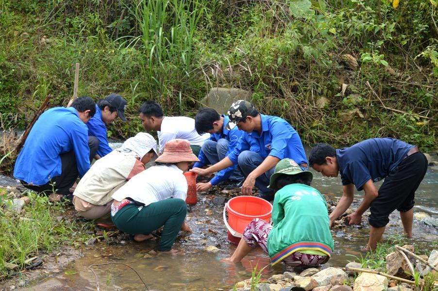 Các đoàn viên nhặt sỏi ở suối để làm hệ thống lọc nước. Ảnh: PHAN VINH
