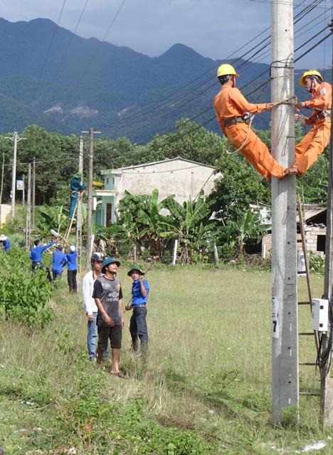 ĐV-TN giúp dân bắt điện chiếu sáng 3km đường giao thông nông thôn. Ảnh: MỸ LINH