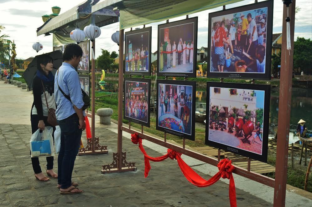 Du khách Nhật Bản chăm chú quan sát các bức ảnh trưng bày trong triển lãm.