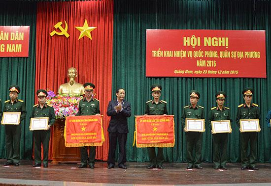 Thượng tá Nguyễn Xuân Hải (bên phải) đại diện lực lượng vũ trang huyện Phước Sơn nhận Cờ thi đua xuất sắc do Chủ tịch UBND tỉnh Đinh Văn Thu trao tặng. Ảnh: TUẤN ANH