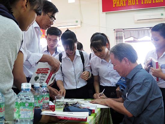 Nhà văn, nhạc sĩ Vũ Đức Sao Biển ký tặng sách cho học sinh Duy Xuyên.  Ảnh: SONG ANH