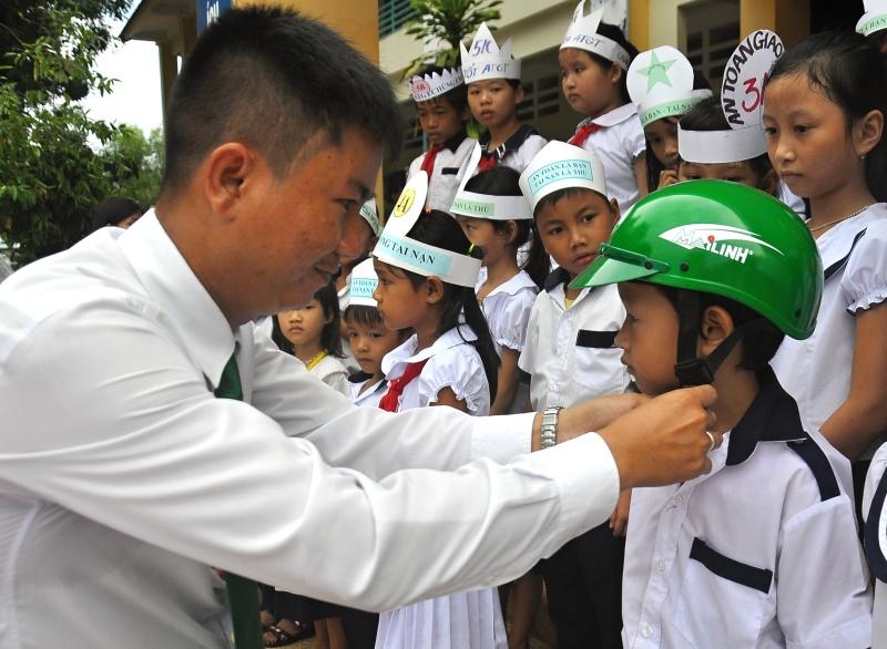 Đại diện taxi Mai Linh Tam Kỳ trao tặng mũ bảo hiểm cho học sinh. Ảnh: V.A
