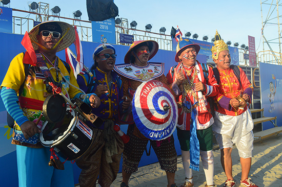 Khamthong (giữa) cùng nhóm bạn bè của mình đang cổ vũ cho một trận bóng đá bãi biển.