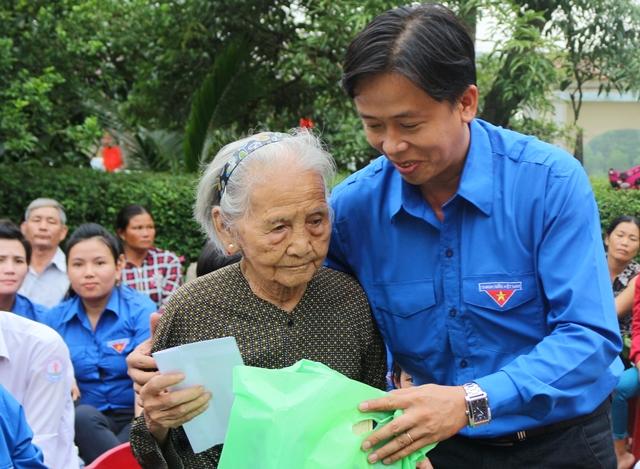 Đồng chí Đinh Nguyên Vũ- Bí Thư Tỉnh đoàn Quảng Nam tặng những món quà tri ân đến gia đình cụ Huỳnh. Ảnh: L.Đ
