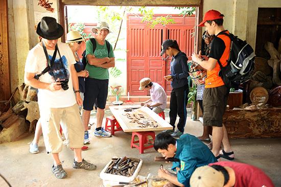 Làng mộc Kim Bồng giữ được lao động trẻ nhờ vừa làm nghề vừa khai thác du lịch. Ảnh: MINH HẢI
