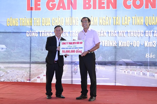 Giám đốc Công ty TNHH Một thành viên Hữu Hay - ông Trần Hay (đứng bên trái) trao tặng 50 triệu đồng ủng hộ đồng bào miền Trung bị ảnh hưởng do mưa lũ. Ảnh: CÔNG TÚ