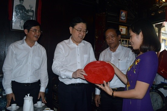 Chairman Zhang Dejiang offers a souvenir gift to representative of Tan Ky old house