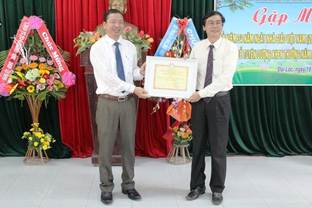 Chủ tịch UBND huyện Trần Văn Mai trao tặng danh hiệu cao quý cho tập thể thầy và trò Trường Đỗ Đăng Tuyển. Ảnh: Bích Liễu