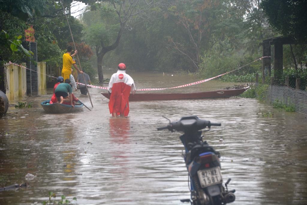 Tuyến đường ĐT615 đoạn qua thôn Vĩnh Bình (xã Tam Thăng) bị ngập nặng khiến cho một số người dân phải dùng xuồng để di chuyển. Ảnh: XUÂN THỌ