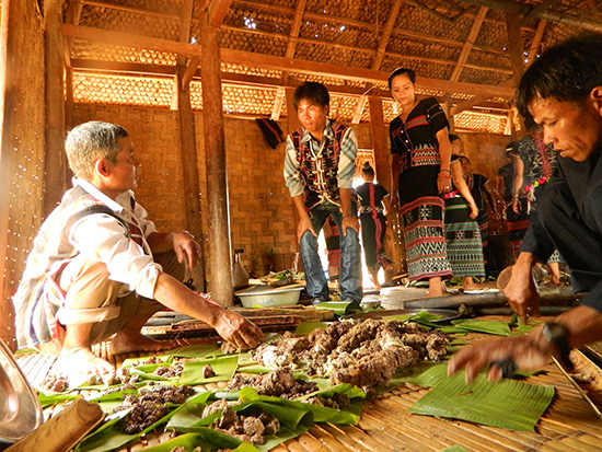 Trưởng thôn Pơrning (xã Lăng, Tây Giang) - Bh'nướch Lạc theo dõi việc chia thịt cho các hộ trong thôn.  Ảnh: BRIU QUÂN