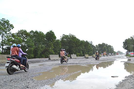 Mặt đường QL1 đang khai thác qua Tam Nghĩa bị hư hỏng nặng nề. Ảnh: C.T